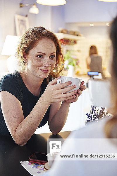 Smiling young woman drinking coffee with friend at cafe