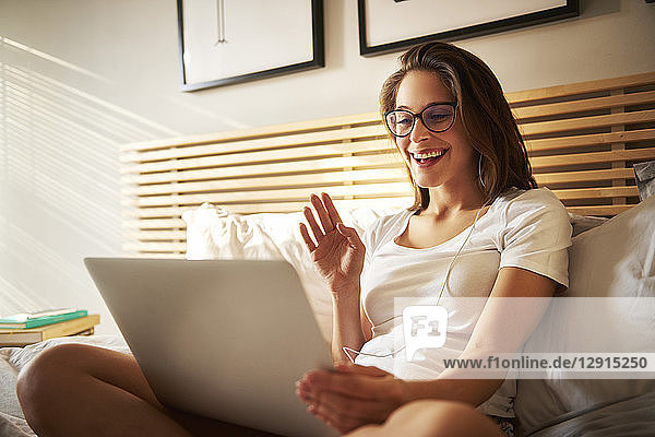 Portrait of laughing young woman sitting on bed with laptop chatting
