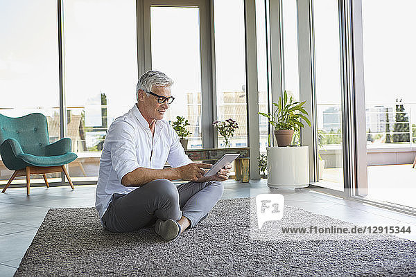 Mature man sitting on carpet at home using tablet