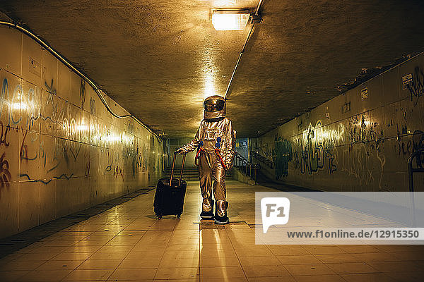 Spaceman in the city at night in underpass with rolling suitcase