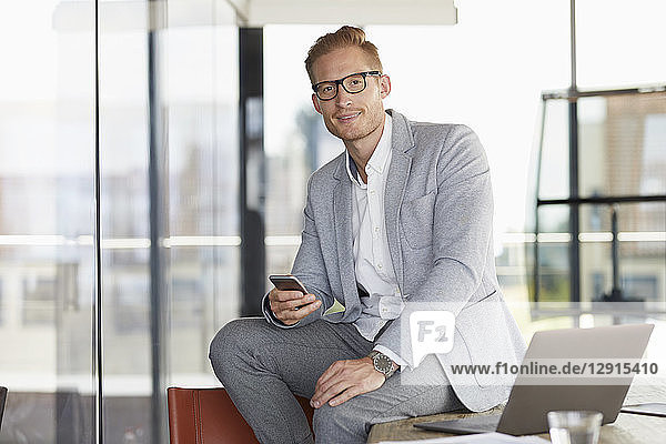 Portrait of smiling businessman with laptop and cell phone sitting on desk in office