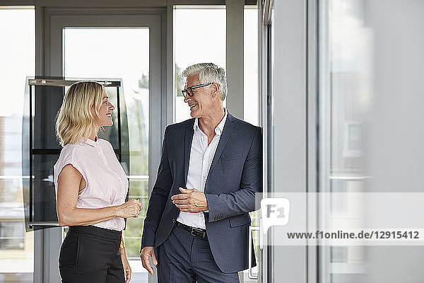 Businessman and woman standing in office  discussing project