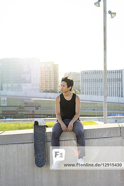 Young man sitting on urban wall next to skateboard at sunset