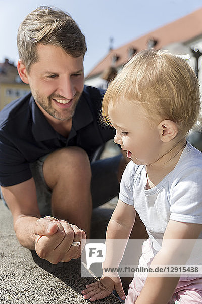 Father making a fist smiling at little daughter outdoors