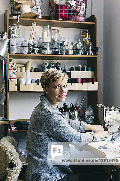 Portrait of confident woman using sewing machine in studio
