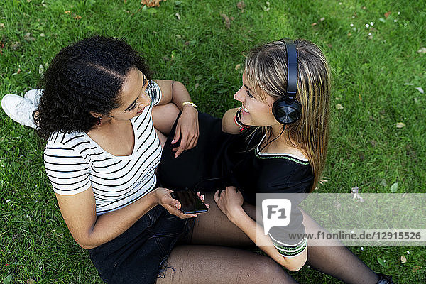 Two girlfriends in a park listening music  using smartphone