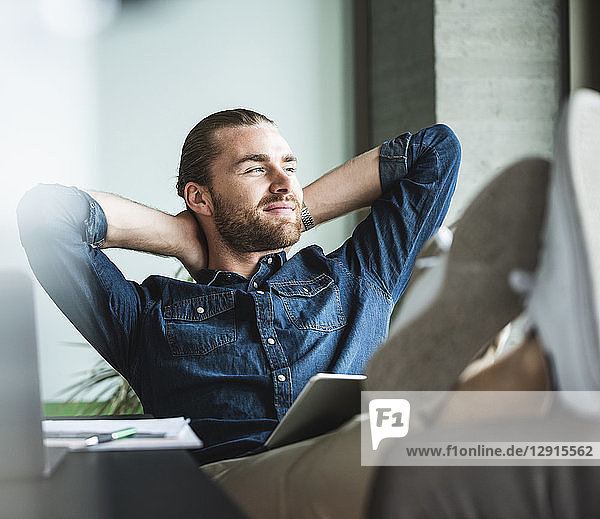 Relaxed smiling businessman sitting in office looking out of window