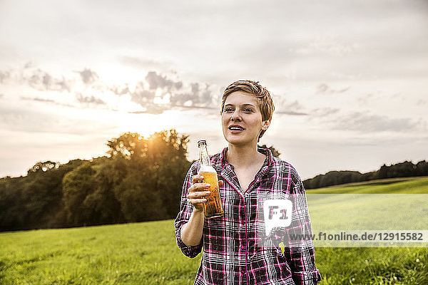 Smiling woman drinking beer in rural landscape