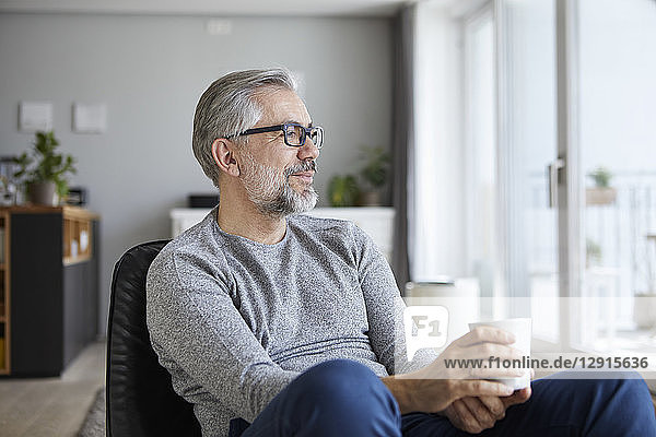 Content mature man relaxing with cup of coffee at home