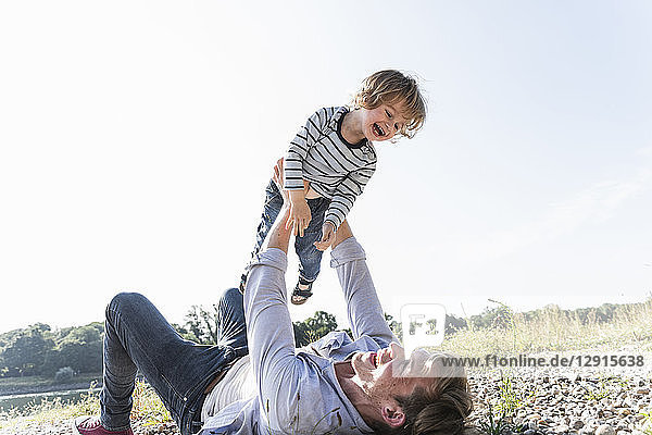 Father and son having fun at the riverside  playing aeroplane