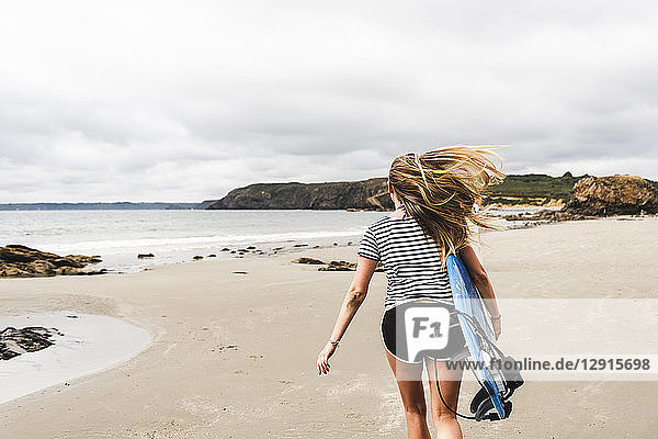 Young woman with surfboard running on the beach