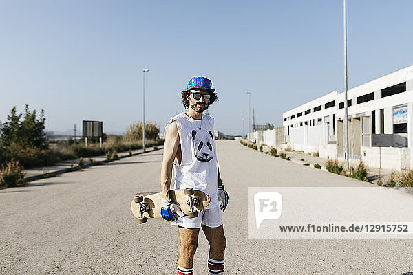 Portrait of sportive man in white and blue with skateboard on empty gray paved road