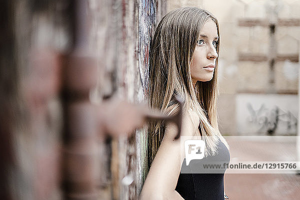 Pensive teenage girl leaning at a wall