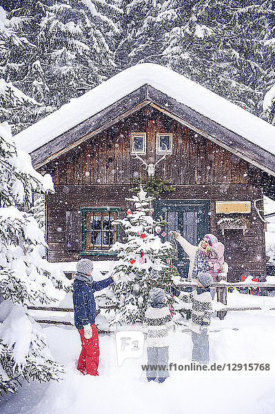 Austria  Altenmarkt-Zauchensee  family decorating Christmas tree at wooden house