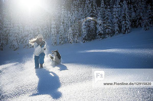 Austria  Altenmarkt-Zauchensee  happy young woman running with dog in snow