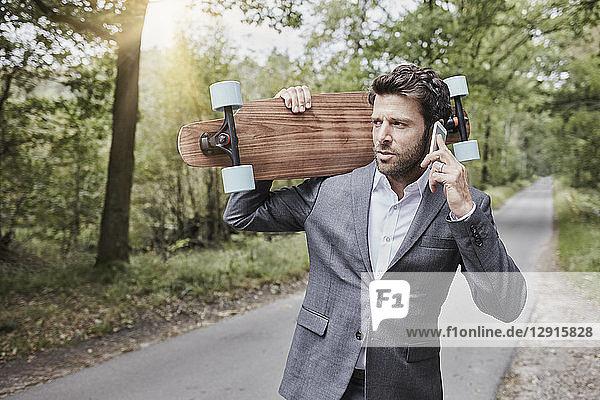 Businessman with skateboard talking on smartphone on rural road