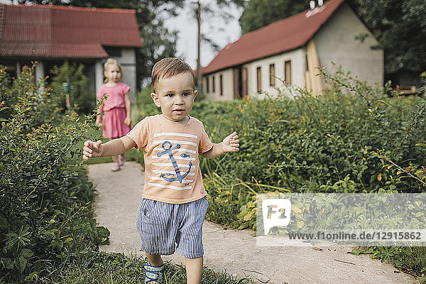 Baby boy walking in garden with sister in background