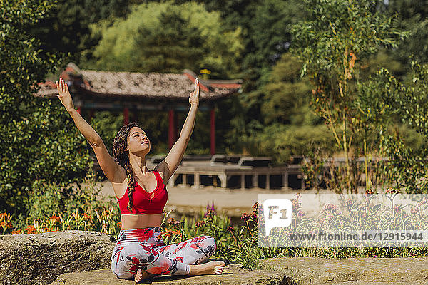 Young woman practicing Pilates in an urban park  raised arms