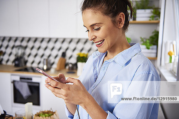 Young woman using smartphone in the kitchen