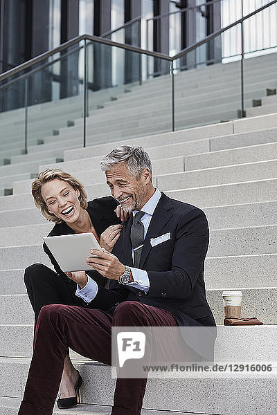 Portrait of two businesspeople sitting together on stairs looking at tablet having fun