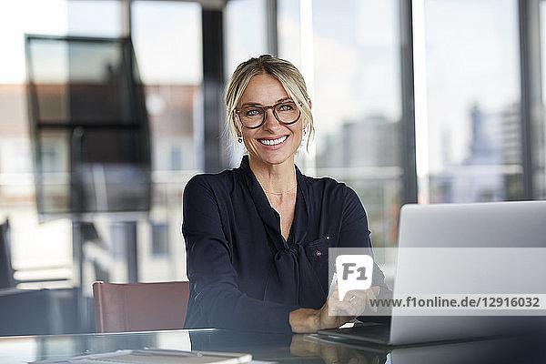 Businesswoman sitting at desk  using laptop  smiling friendly