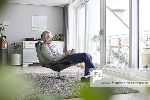 Mature man sitting on leather chair in his living room relaxing with cup of coffee