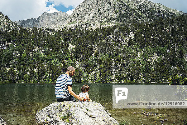 Spain  Father and daughter sitting on a rock at a mountain lake  feeding ducks
