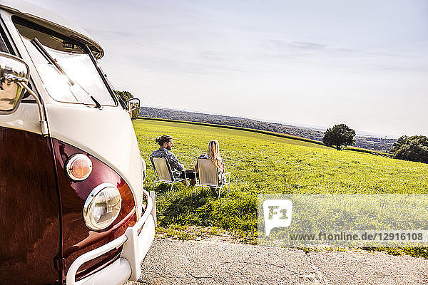 Couple sitting on camping chairs next to van in rural landscape