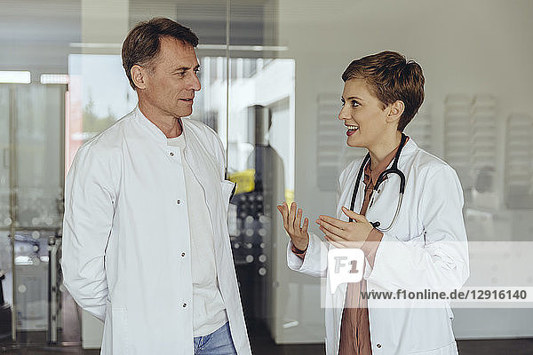 Two confident doctors standing in practice  discussing