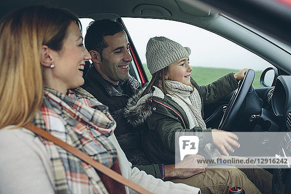 Happy family in car with little girl on father's lap pretending to drive