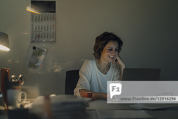 Businesswoman working overtime  using laptop