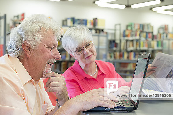 Senior couple with laptop and newspaper in a city library