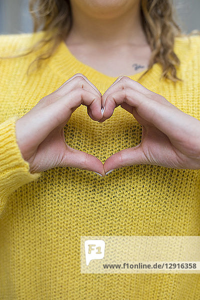 Young woman shaping heart with her hands  close-up