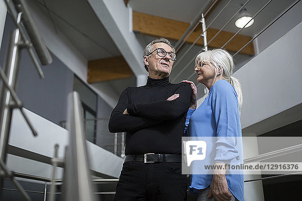 Senior woman supporting senior businessman on office stairs
