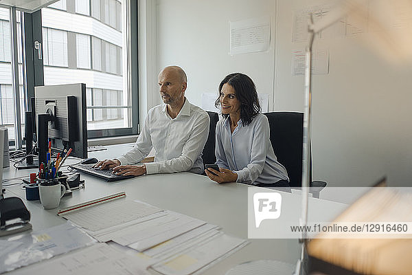Businessman and woman working together in office