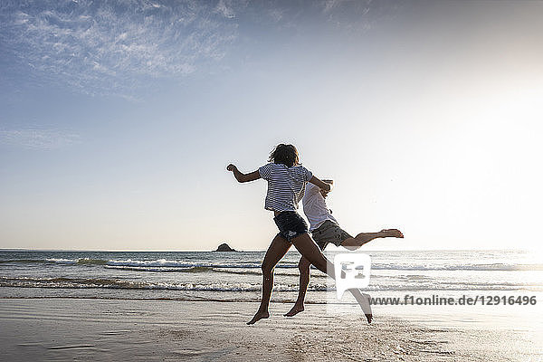 Young couple having fun on the beach  running and jumping at the sea