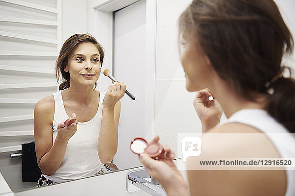 Mirror image of smiling young woman applying Makeup in bathroom