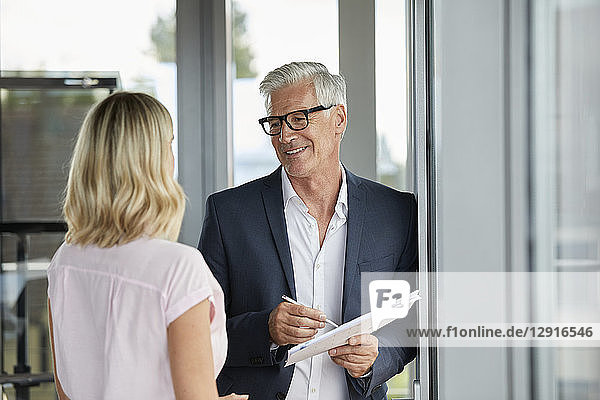 Businessman and woman standing in office  discussing project  holding documents