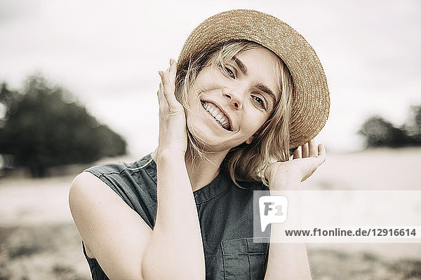Portrait of smiling young woman wearing straw hat