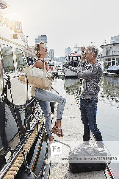 Older man taking picture of young woman on jetty next to yacht
