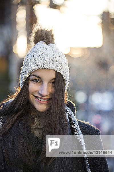 Portrait of smiling young woman wearing bobble hat in winter