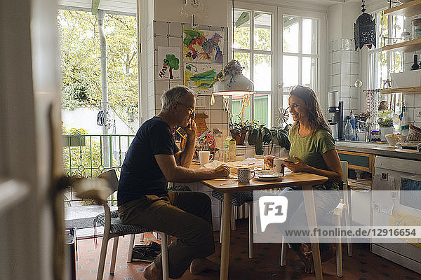 Mature couple sitting at kitchen table at home