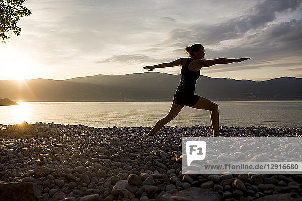 Young woman doing yoga at the stony beach at sunset  Warrior pose