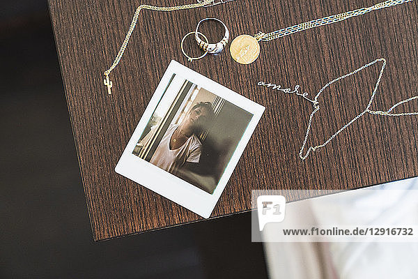 Instant photo of young woman next to jewelry on wooden table