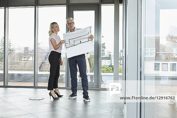 Businessman and woman standing in office  discussing blueprint
