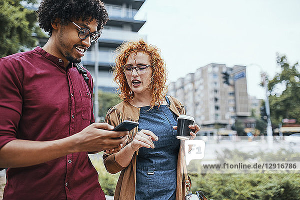 Colleagues walking in the city  talking  using smartphone