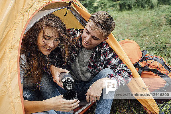 Young couple sitting in tent  drinking tea