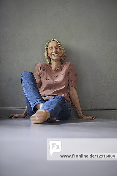 Portait of smiling mature woman at home sitting on the floor