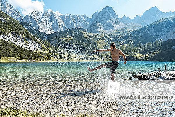 Austria  Tyrol  Young man at Lake Seebensee kicking water  having fun