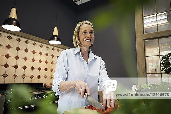 Smiling mature woman chopping bell pepper in kitchen